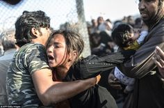One young girl was pulled through the barbed wire fence as the Syrian refugees desperately...