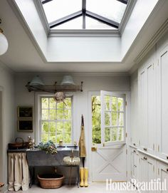 A skylight gives the mudroom the air of a conservatory. The soapstone sink is used for flower arranging and bathing the family's two King Charles spaniels, who come in and out through a louvered dog door at the base of the floor-to-ceiling cabinets.