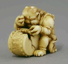 A small ivory Netsuke, c.1870, of an Oni crouched over a broken drum and dissatisfied with his musical attempt, signed Ryuju, 2.4cm