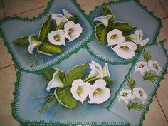 Tapetes emborrachados, pintados à mão, motivo copos de leite, com barrados em crochê, copmposto por: 2 tapetes de chão, 1 tapete para o vaso e 1 porta papel higiênico.