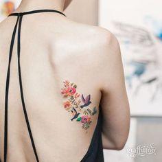 Un tatouage fleuri aux couleurs pastel dans le dos