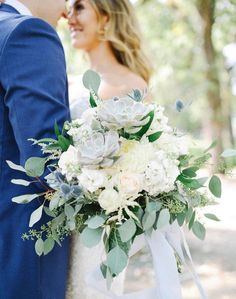08b5d16d06633 Cream and pale blue florals for a natural looking bridal bouquet. Greenery,  roses, astilbe, succulents, eucalyptus, football mums, and pale blue ribbon.