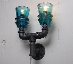 Industrial style wall sconce with 2 vintage green glass insulators. $162.14, via Etsy.