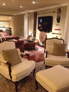 Florida-Room/porch with Thomasville chairs (which look out onto the golf course), showing the living room behind the chairs, with flat-screen TV and sound bar mounted on right wall.