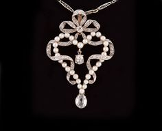 Edwardian Natural Pearl Diamond Gold Pendant. The 18 karat yellow gold backed, platinum topped pendant is in the shape of a heart, formed by natural pearls intertwined with a narrow ribbon of platinum bead-set with small diamonds forming a bow at the top. Within the center hangs a prong-set larger diamond, and a pear-shaped briolette diamond is suspended from the bottom. The pendant is attached to a platinum chain composed of elongated filigree links alternating with small white round pearls