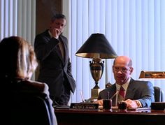 Skinner speaks to Scully while the smoking man lurks in the corner.