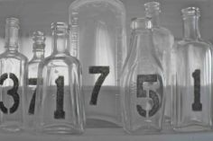 Table numbers on clear bottles!  This would look cool, too, if they were on upside down wine glasses with a single bud underneath each one to add color!
