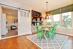 Dining room with bright green chairs, corner coffee station and sliding style barn door [Design: Lavender Design Group]