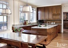 #Vaughn #light #fixtures hang over the table and benches by Bausman adding intimacy to this #classic #traditional #kitchen... #Luxe