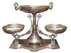 Fruteira em metal prateado art nouveau, com três bandejas redondas, duas com (20cm de diâmetro) e uma com (27cm de diâmetro e duas alças), bordas com flores e arabescos, corpo e base com guirlandas (40x60x10cm).