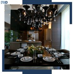 A metal and crystal chandelier takes center stage in this dining area. Dark accents against white flooring and cutlery gives it an uptown feel. White Flooring, Interior Architecture, Interior Design, Center Stage, Urban Planning, Cutlery, Dining Area, Table Settings, Chandelier