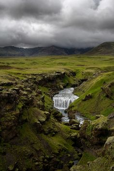 Impressive Skógafoss waterfalls in  Iceland. I love the moss and dark hanging clouds. So msytic!