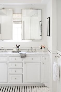 This chic all white bathroom has marble countertops, white vanity cabinets, dual sinks, and double vanity mirrors.
