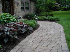 Outdoor and Patio Curved Stone Walkways Designs For Homes With Sweet Garden And Two Small Garden Lamps Also Green Grass Yard And House With Brick Wall And Two Doors Also Two Outdoor Lamps Get Your Steps More Enjoyable By Creating The Charming Walkway Designs For Homes