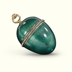 A Fabergé enamelled gold egg vinaigrette, workmaster Michael Perchin, St Petersburg, circa 1892, enamelled in translucent fir green over scale engine-turning, the rim set with a band of diamond chips, the grille pierced: 1892, pendant loop.