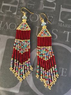 Long fringe beaded earrings made with spiral red bugle beads and stunningly…