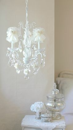 """Light up your room. With crystal prisms and cream dupioni silk shades decorated with generous cream tulle bows, satin ribbons and matching mulberry roses in full bloom, the chandelier will dress any room with loads of sparkle, romance and charm. Perfect for a nursery, little girls bedroom, or breakfastnook. <BR><BR> • Cottage White<BR> • Handmade to order<BR> • Ready to hang <BR> • Detailed glass neck <BR> • Glass bobeches<BR> • Drip-candle covers<BR> • 13""""W x 20""""L<BR> • Comes with ..."""