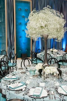 Giant spheres of fresh gypsophila blossoms atop metallic trumpet vases topped tables, where ivory roses sat in vintage garden urns and blue mercury glass votive containers.