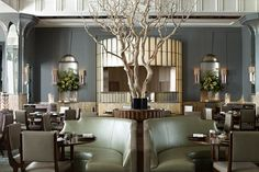 Interior designer Guy Oliver wrapped the perimeter of Fera, the new farm-to-table restaurant in London's legendary Claridge's hotel, with a band of honey and amber onyx. The room also has calm gray walls, leather banquettes in soft green, sage curtains and carpets, and a dramatic sandblasted manzanita tree at the center.