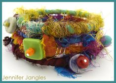 "Wrapped Bangles   Supplies:   Plastic bangle  2 feet silk sari ribbon  Accent bead  4"" headpin   Instructions:  Step 1. Starting about 2 i..."
