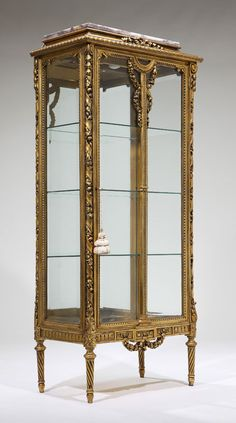 A Louis XVI style giltwood vitrine cabinet, he rectangular purple and white mottled marble top above a molded downswept frieze with gadrooned rim above a beveled glazed paneled door, with central garland entwined guilloche band, enclosing three glass shelves, with beveled glazed sides, on turned tapering spirally fluted legs.