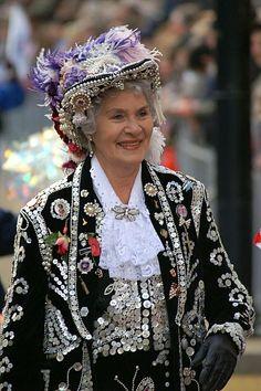 """Pearly Queen  La tradition londonienne des """"Pearly Kings and Queens"""" a commencé en 1875, quand Henry Croft, un garçon âgé de 13 ans, décida d'aider les gens dans le besoin en attirant l'attention sur lui. Pour cela, il fabriqua un costume totalement recouvert de boutons en formes de perles  Pour recueillir davantage d'argent, Henry eut l'idée de demander à ses amis de porter le même type de costume que lui. Ainsi, « The Pearly Family » était née."""