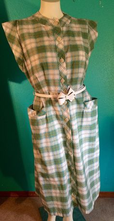 This is a TRUE VINTAGE handmade timeless dress. It has a look of the 1940s, 1950s and early 60s. I believe its early 1960s. Sage green plaid with a light cream plastic bow belt. Turquoise blue and black accent lines running throughout the entire dress. The buttons are plastic that have a iridescent shine to them. The sleeves are incredible, and the two side pockets are a great touch! Its well made with detailed pleats. Cotton & rayon blend . $45.00 plus $7.00 shipping Measurements: Waist-...