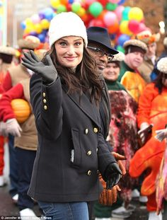 Idina Menzel dressed warmly in a black double-breasted coat,