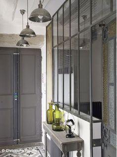 Adieu au petit couloir tristounet grâce à l'aménagement d'une verrière intérieure dans l'entrée ! Une idée astucieuse pour agrandir l'espace et faire entrer la lumière