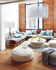 Steinwände, Paletten-Sofa und riesen Lampe. Schönes modernes Wohnzimmer