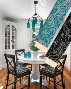 White table, Black chairs, Black and White cushions. Aqua blue.