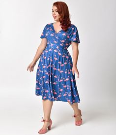 Ready for a summer swoon, gals? Vibrant and vivacious, this plus size faux-wrap dress is soft and stretchy, crafted in a lightweight knit blend in a 1950s swing design. A lush blue backing is peppered with bright pink flamingos, complete with short sleeve