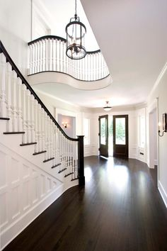Railing Idea Grand formal foyer with dark hardwood floors and double front doors. Sweeping paneled staircase with white spindles and dark handrail. Curved balcony overlooking stairs, white walls and large glass and iron pendant. Style At Home, Floor Stain Colors, Interior Design Minimalist, Dark Wood Floors, Dark Flooring, Laminate Flooring, Wood Paneling, Foyer Flooring, Garage Flooring