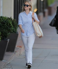 In the jeans: Reeseteamed her chic top with a pair of faded bootcut jeans, which casually...