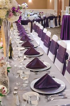 Head Table Details for a Wedding Reception held in our Grand Ballroom with seating for 280 guests. Featuring ceiling draping and a crystal chandelier! Accenting the room with fresh floral arrangements and and color palette of plum, silver & white!