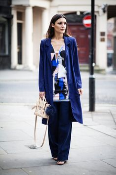 Anisa Sojka wearing blue / black / white Three Floor abstract prep and print dress as a top, blue Few Moda wool wide leg trousers, blue oversized Never Fully Dressed long light coat, gold / silver / bronze OMG Rebus signet rings, beige 3.1 Phillip Lim mini pashli cross-over bag and black Nly sandal heels. Fashion blogger street style shot in London by Cristiana Malcica.