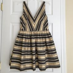 J.Crew petite gold and gray v neck flared dress Such a fun party dress with pockets! Flattering v neck and flare effect! NWT. Lined. 54% cotton, 43% polyester, 3% other fiber. 33 inches long. Size 6 PETITE. J. Crew Dresses