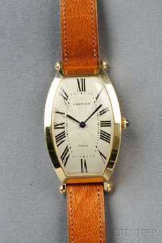 """Sale 2575B, Lot 334   18kt Gold """"Tonneau"""" Wristwatch, Cartier, Paris, the ivory-tone guilloche enamel dial with Roman numeral indicators, enclosing a 17-jewel manual-movement, completed by a brown strap, no. 35 IV, A103602, maker's mark and guarantee stamps, signed.   Sold for $4,148.00"""