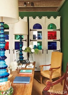 Deep green walls encompass Gothic Revival Cabinets with custom colored-glass insets.