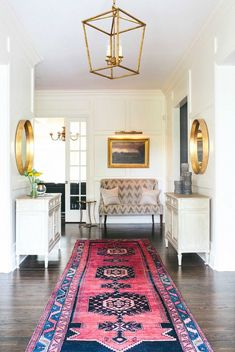 White and gold entryway with Persian rug and mirrors lining hallway