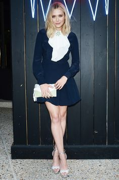Elizabeth Olsen wears a navy Miu Miu dress with a white ruffle neck and metallic sandals