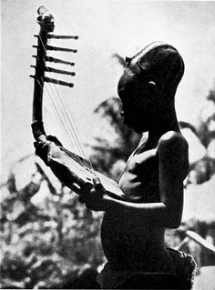 A Mangbetu (Democratic Republic of the Congo) man playing a bow harp