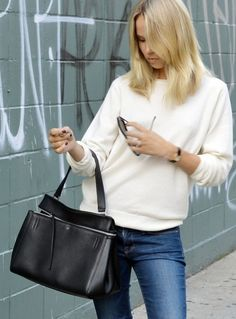 Simple style. White sweater, blue jeans, leather bag, black nails
