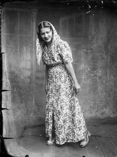 Beauty: A woman poses in a long patterned dress with head scarf and chunky sandals Photo by Costica Acsinte #romania #vintage #blackandwhite