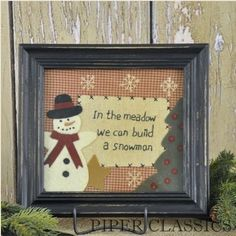 """In The Meadow Stitchery - Displayed in a 10"""" x 9"""" time-worn black frame, this framed stitchery under glass, is appliquéd and hand embroidered with the saying """"In the meadow we can build a snowman"""". Ready to hang or use with a photo easel. #rustic country art @homespun crafts #christmas prim decor"""