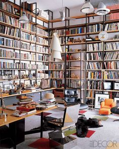 Eames lounge chairs, vintage industrial lights, and custom-made shelving by Gerben Mulder in the library; the carpet panels are by Flor, the mobile sculpture is by Man Ray, and the steel chair is by Ron Arad.