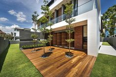 Modern Roadside House Design with Wooden Flooring: Wooden Deck Outdoor Patio With Tree And Green Lawn Also Surrounding Fence ~ daily-inspirations.com Decorating Ideas Inspiration