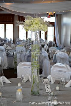 Tall vases with babies breath filled with water and hydrangeas on top with silver glittered leaves.