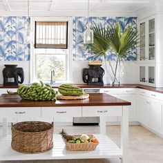 """""""Mahogany countertops give the kitchen age, and fit in better than the sleekness of stone. I also try to work in a few fun elements to add character, like the palm wallpaper and wicker elephants, to balance the sheen of the appliances."""""""