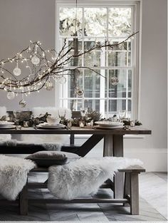 Scandinavian Christmas setting with lights and ornaments. A magical Scandi Christmas table with candles and fairy lights and sheepskin rugs to add hygge to this Christmas table
